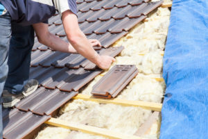 roofing contractors laying a tile on the roof
